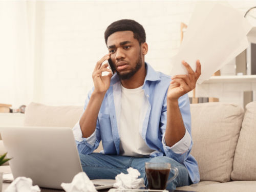 upset man on phone talking about chapter 13 bankruptcy in front of computer