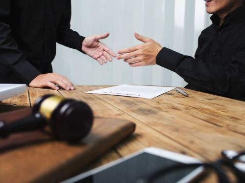 two people in front of a table shaking hands over a legal document