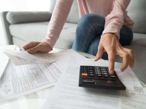 woman using calculator while surrounded by bills