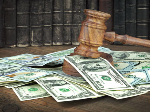 gavel on a table scattered with money