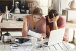 Young couple doing paperwork in kitchen