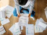 woman sitting on floor going through bills