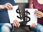 man and woman holding two halves of money symbol paper