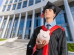 college graduate holding a piggy bank to pay student loans